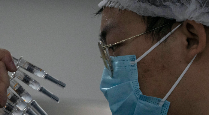 A worker inspects syringes of a vaccine
