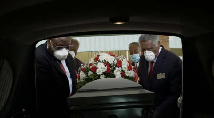 A casket is loaded into a hearse