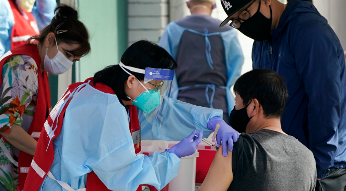 A health care worker receives a COVID-19 vaccination
