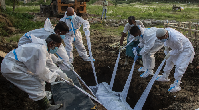 Relatives and municipal workers in protective suit bury the body of a person who died due to COVID-19 in Gauhati, India
