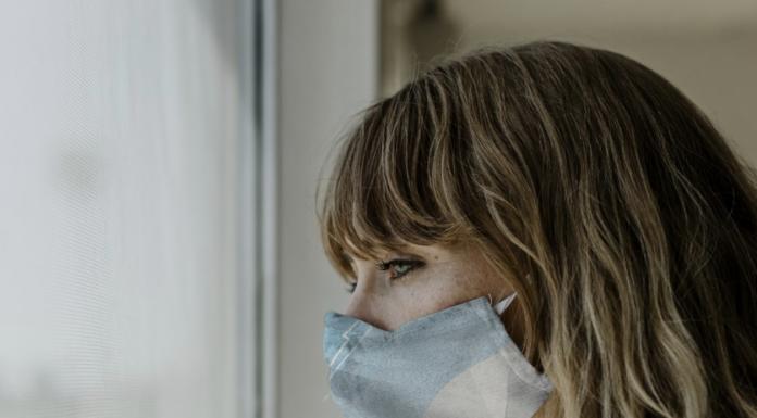 Woman wearing mask gazing out a window