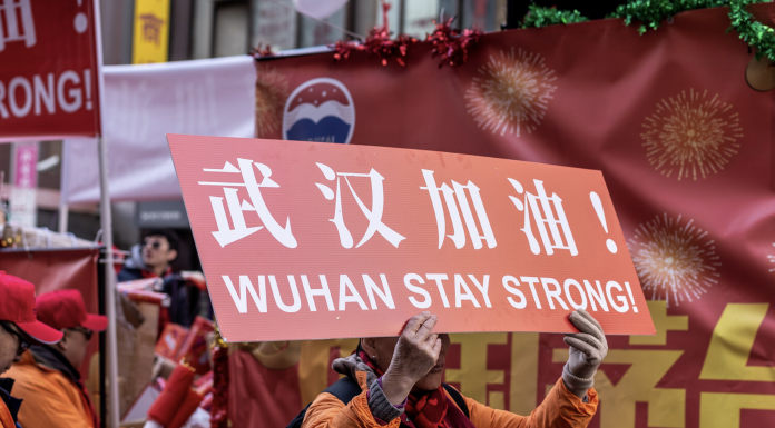 Person carrying a sign that reads 'WUHAN STAY STRONG'
