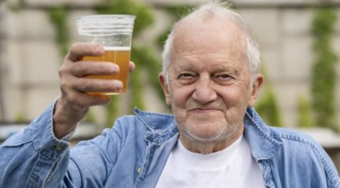 George Ripley of Washington holds up his free beer after receiving the J&J COVID-19 vaccine shot