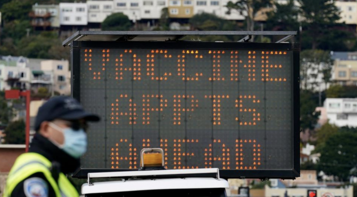 An officer stands in front of a sign advising of vaccine appointments at a drive-up vaccination center at City College of San Francisco during the coronavirus pandemic in San Francisco. San Francisco city workers will be required to be vaccinated against the coronavirus when a vaccine receives full federal approval. The policy covering 35,000 municipal workers may be the first by any city or county in the U.S., the San Francisco Chronicle reported Wednesday, June 23, 2021.